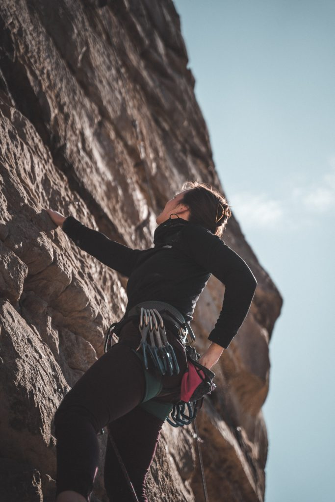 woman in black long sleeve shirt and blue denim shorts climbing brown rock formation during daytime